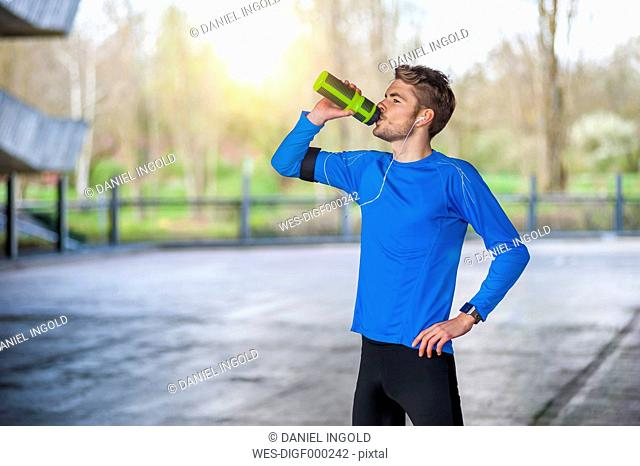 Young sporty man with water bottle