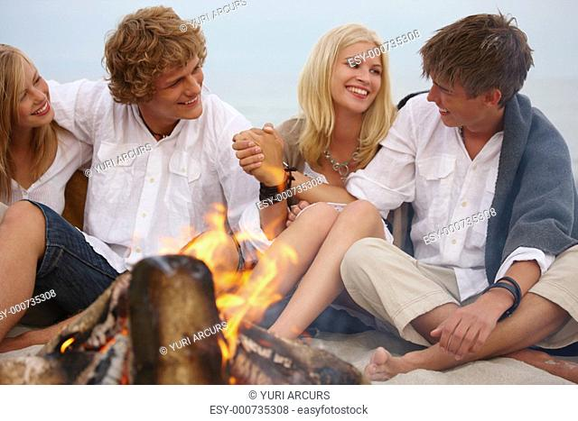 Happy young friends sitting in the sand on the beach by the fire Having a romantic time