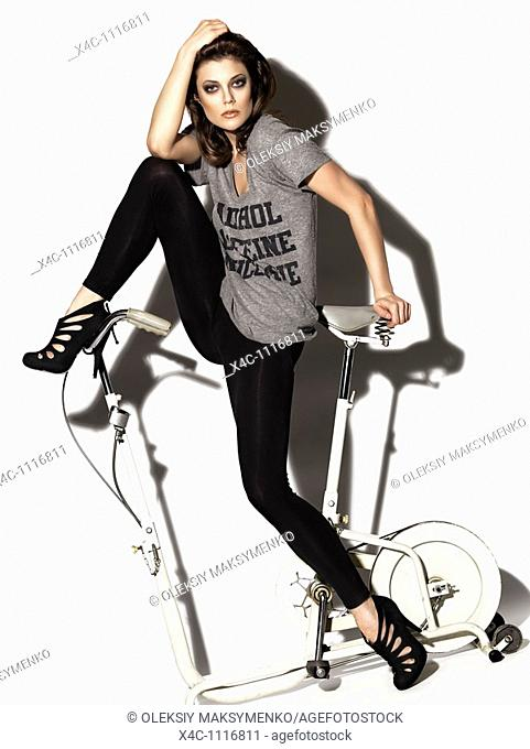 Young woman in a T-shirt and leggings posing on a retro exercise bike  Edgy high fashion photo