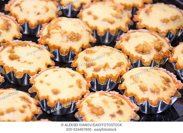 A view of several freshly baked cakes in metal tins