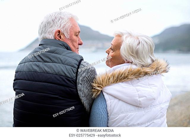 Senior couple sitting on rock at beach