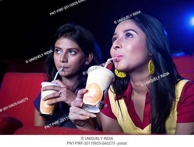 Two female friends enjoying soft drinks while watching movie in a cinema hall