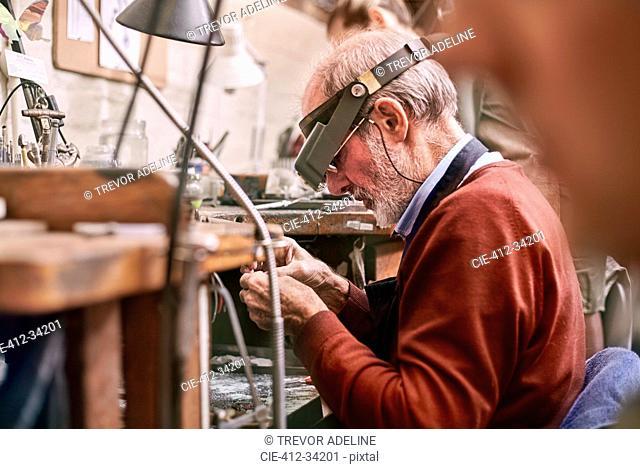 Jeweler wearing headband magnifier working in workshop