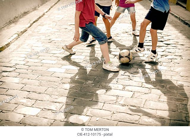 Children playing with soccer ball on cobblestone street