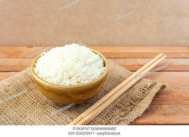 White rice in brown bowl with wood chopsticks on wooden background