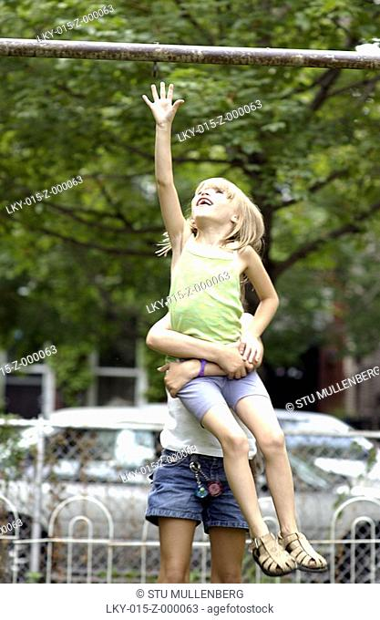 Young girl reaching for horizontal pole with the help of another girl