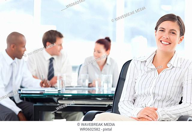 Smiling businesswoman with meeting being held behind her