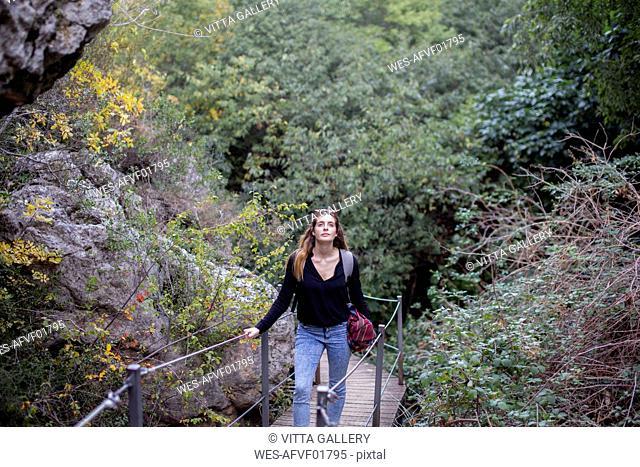 Spain, Alquezar, young woman on a hiking trip walking on boardwalk