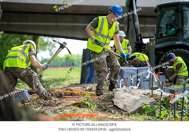 dpatop - 03 May 2018, Germany, Paderborn: Soldiers of the British military police take soil samples next to the river Alme