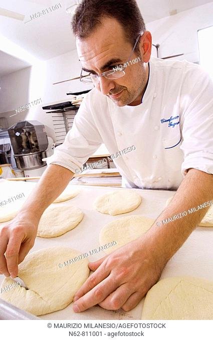 baker cutting the dough to make bread in the oven