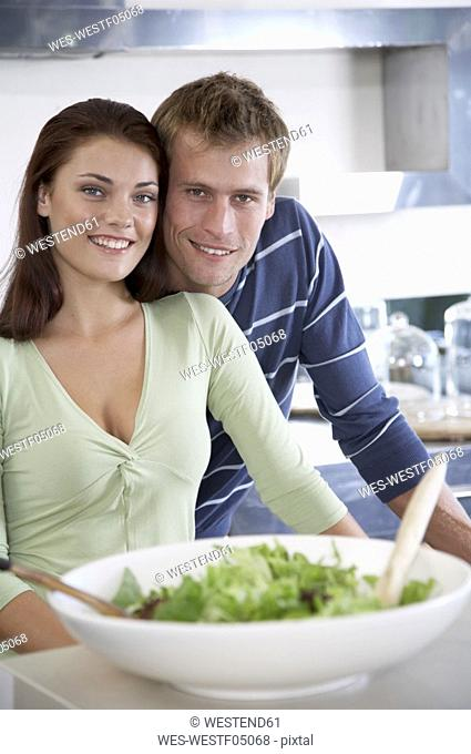 Young couple in kitchen with salad bowl