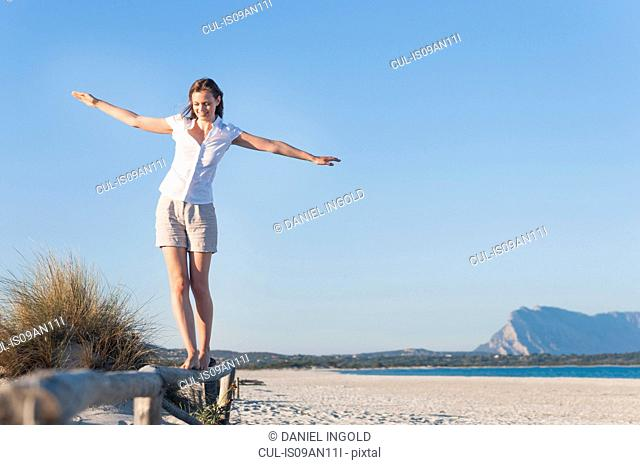 Woman walking on log fence at beach