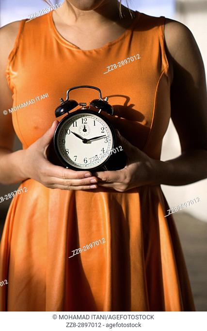 Close up of a young woman holding a vintage alarm clock