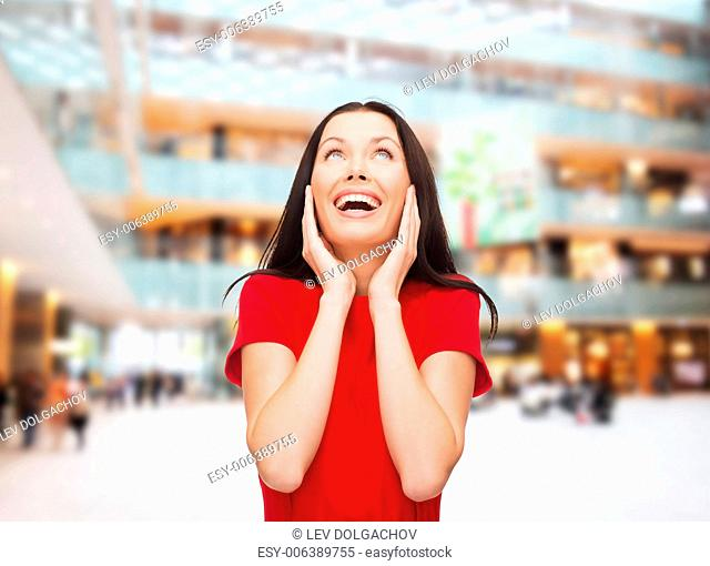 christmas, holidays, valentine's day, celebration and people concept - smiling woman in red dress over shopping center background