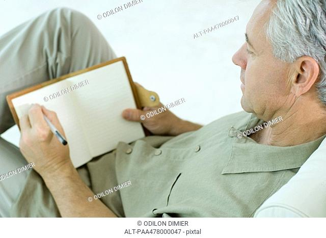 Mature man writing in diary