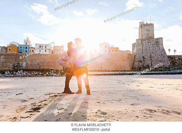 Italy, Molise, Termoli, young couple in the beach at sunrise
