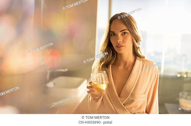 Portrait serious, confident woman in bathrobe drinking water