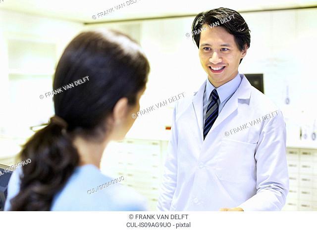 Male pharmacist handing prescription to customer
