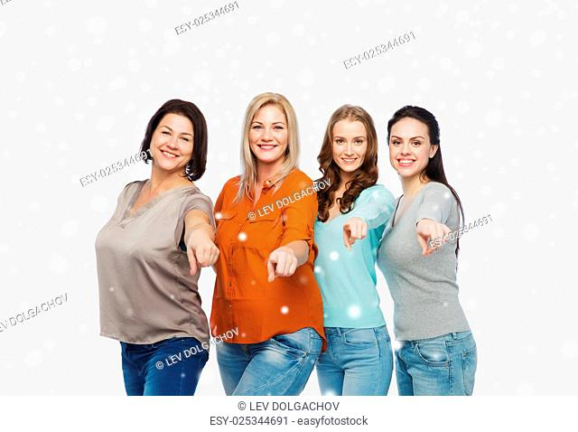 choice, friendship, fashion, diverse people concept - group of happy plus size women in casual clothes pointing finger on you over snow