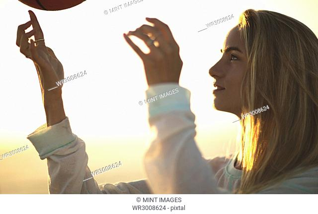 Young woman standing in front of a sunset spinning a basketball on her finger