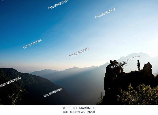 Silhouette of distant man on mountain peak, Passo Maniva, Italy
