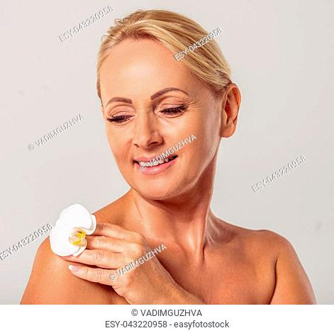 Portrait of beautiful middle aged woman with bare shoulders holding a flower of orchid, looking at it and smiling, on a gray background