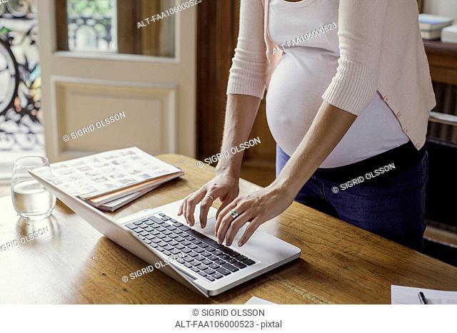 Pregnant woman using laptop computer