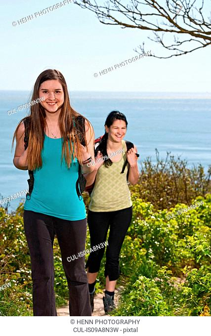 Two female friends walking up coastal path