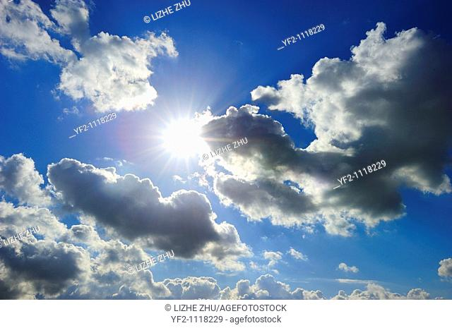 cloudy blue sky with bright shiny sun