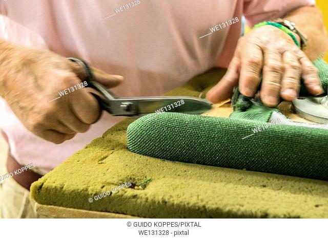 Tilburg, Netherlands. Hands of the 72 year old upholsterer 'Boy', handling a pair of scissors, cutting a piece of cloth