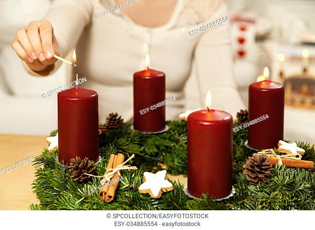 Woman lights fourth candle from Advent wreath