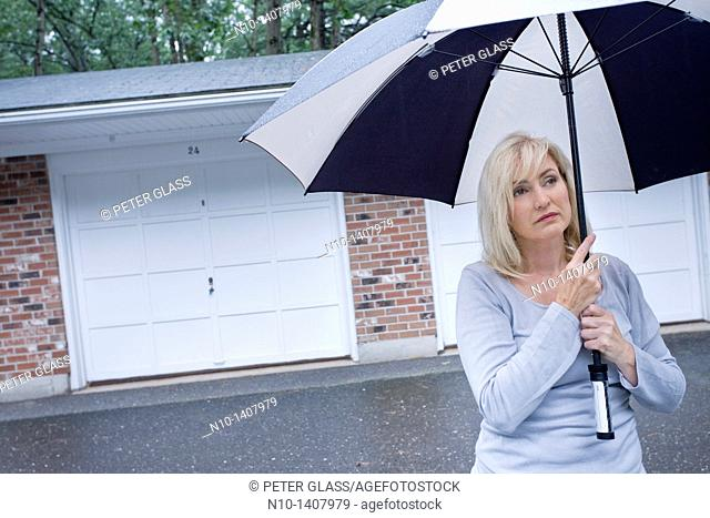 Middle-age blond woman in the rain with an umbrella