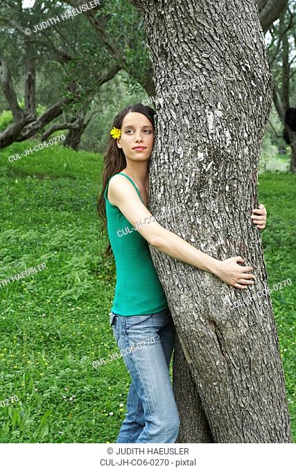 Young woman standing at olive tree she is hugging the tree with both arms eyes open olive trees in background