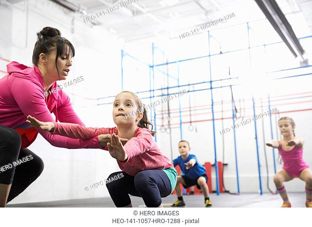 Coach assisting girl with squats in Crossfit class