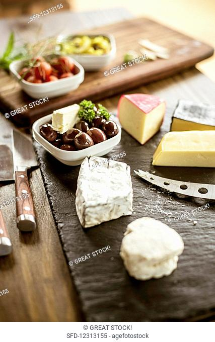 Various types of cheese and olives on a slate platter