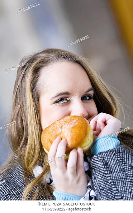 Teen girl peeking behind donut with messy nose