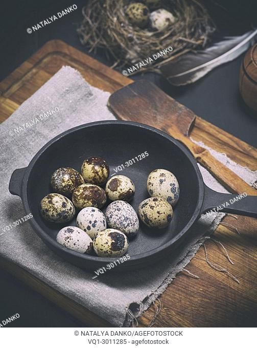 raw quail eggs in the shell lie in a black cast-iron frying pan, vintage toning