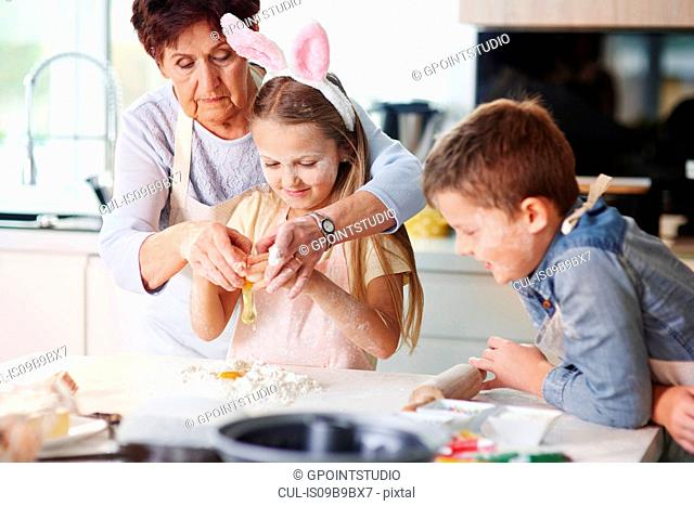 Grandmother helping girl to easter bake at kitchen counter
