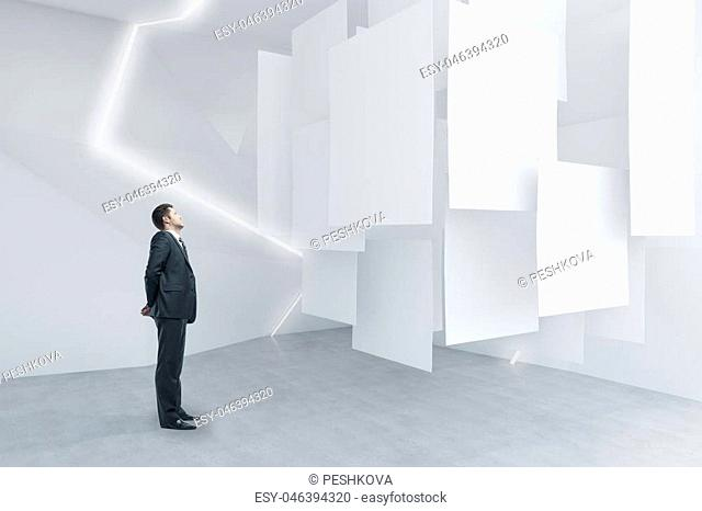 Businessman looking at empty posters in abstract exhibition room. Mock up, 3D Rendering