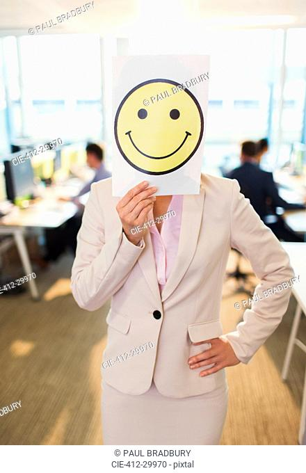 Portrait of businesswoman holding smiley face printout over her face in office
