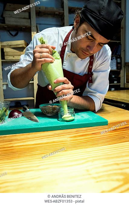 Man putting avocado cream with a pastry bag in a glass jar