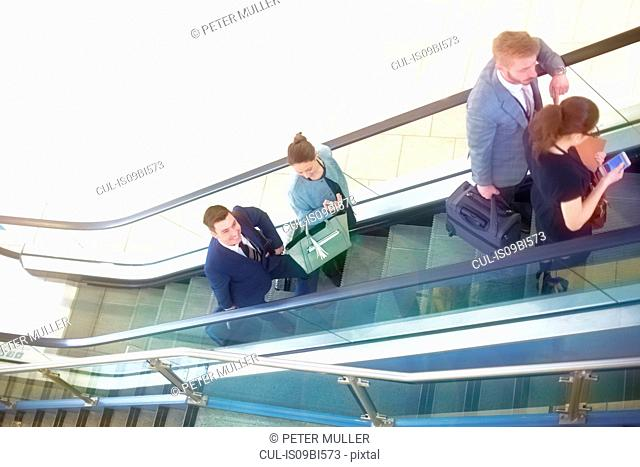 Businessmen and women moving up airport escalator, high angle view