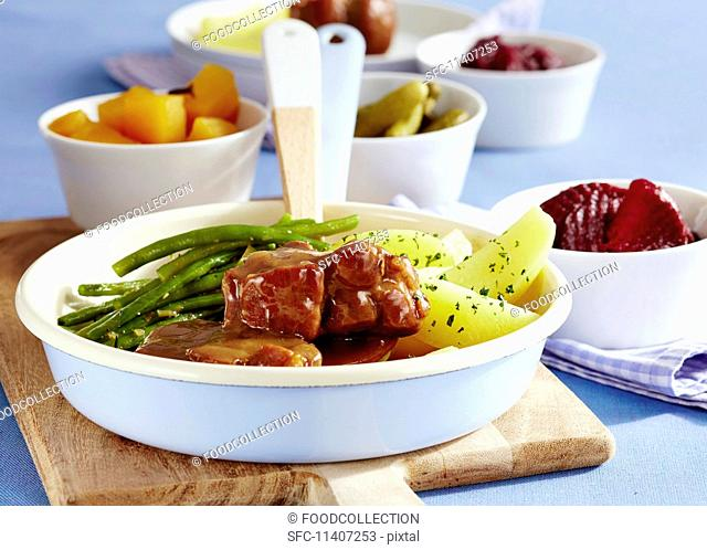 East Frisian Snirtjebraten (roast pork with spices and onions) with potatoes and green beans