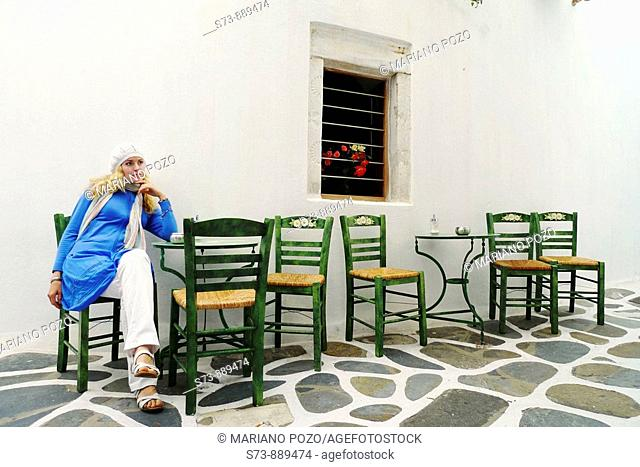 Womaan sitting in a restaurant, Mykonos, Cyclades Islands, Greece