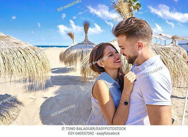 young couple hug in a beach with parasol at summer