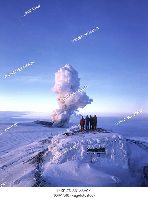 Volcanic eruption in Grimsvotn, Vatnajokull, Iceland in December 1998. Tourists watching from the Roof of a Lodge