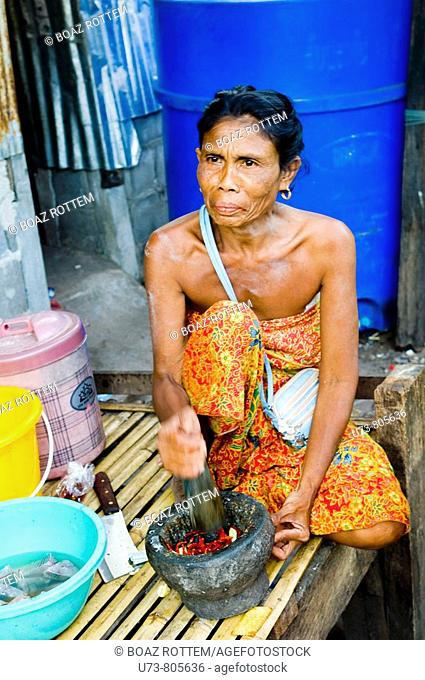 An old Sea Gypsy woman grinds red chilli in preperation for dinner
