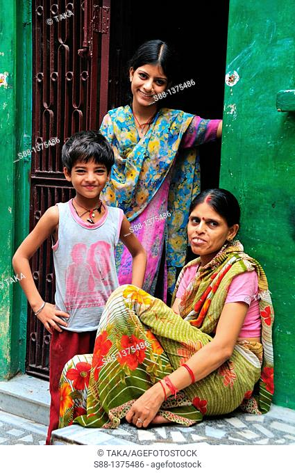 Family at narrow street of old town near the Ganges River