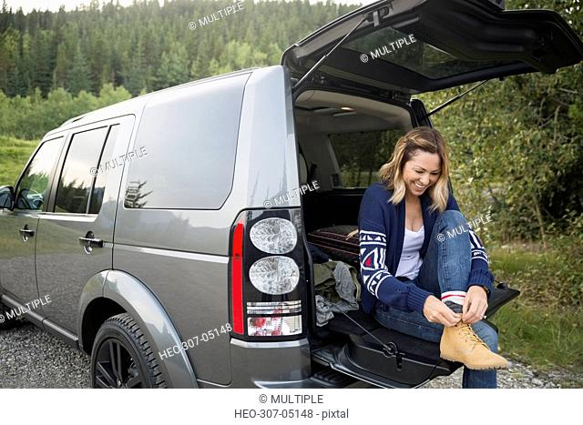 Smiling woman putting on hiking shoes at back of SUV
