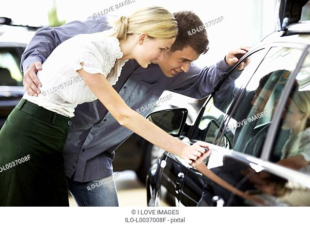 A young couple admiring a new car